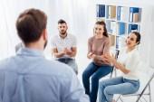 usmívající se lidé tleskají při pohledu na muže během skupinové terapie