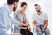 muži utěšující depresivní žena během skupinové terapie