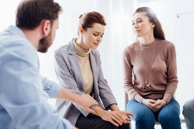 man consoling depressed woman during group therapy session