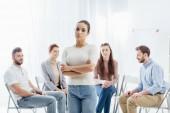 žena s rukama zkříženýma na kameru, zatímco sedí na židlích, během skupinové terapie