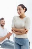 Selektivní fokus usmívající se žena s rukama-překřížené během sezení