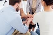 částečný pohled lidí sedí a stohování rukou během skupinové terapie
