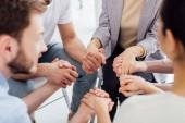 oříznutý pohled lidí drží za ruce během skupinové terapie