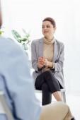 Selektivní fokus ženy v formální oblečení sedí a hledat dál během sezení