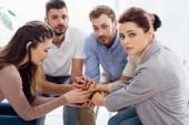 Fotografia gruppo di persone che si siedono e accatastamento mani durante la sessione di terapia