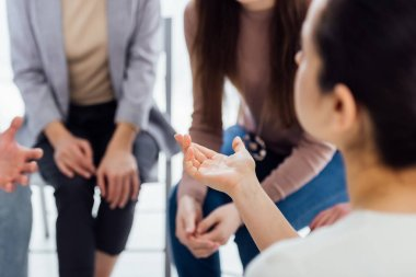 back view of woman gesturing with hand during group therapy session with copy space