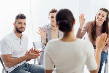 selective focus of people sitting and raising hands during group therapy session
