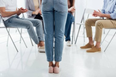 back view of woman standing in front of group of people during therapy session