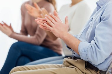cropped view of people sitting and applauding during group therapy session