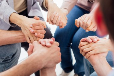 cropped view of people holding hands during group therapy session