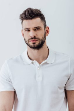 handsome bearded man in white polo shirt looking at camera isolated on grey