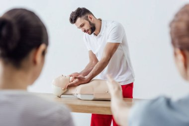 selective focus of handsome instructor with cpr dummy during first aid training class