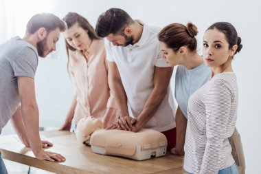 Woman looking at camera while group of people performing cpr on dummy during first aid training stock vector