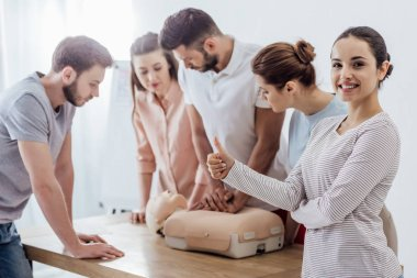 woman showing thumb up while group of people performing cpr on dummy during first aid training