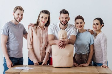 Group of people with cpr dummy looking at camera and smiling during first aid training class stock vector