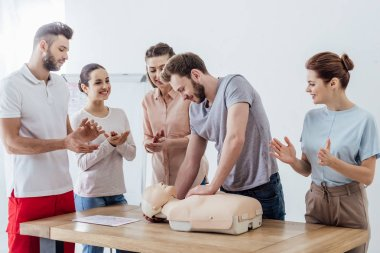 Group of people applauding while man performing cpr on dummy during first aid training stock vector