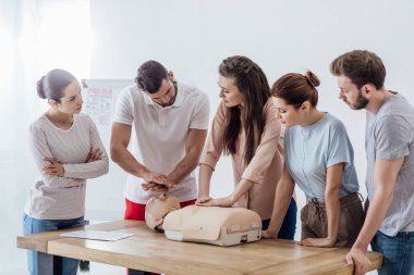 group of people with instructor performing cpr on dummy during first aid training
