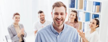 panoramic shot of smiling man looking at camera while people sitting during group therapy session