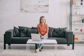 Krásná blondýna freelancer sedí na pohovce nedaleko laptop doma
