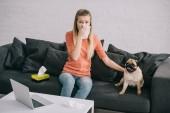blonde Mädchen Niesen im Gewebe sitzend mit Mops Hund auf sofa