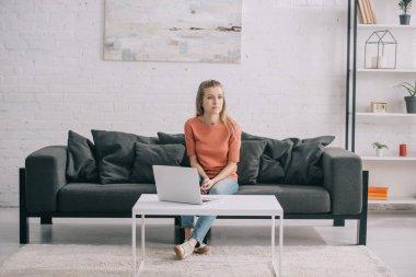 beautiful blonde freelancer sitting on sofa near laptop at home
