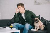 szép ember allergiás a kutya segítségével inhaláló mopszli kanapéra ülve