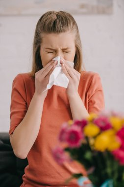 selective focus of blonde woman with pollen allergy sneezing in tissue with closed eyes near flowers