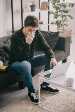 sick man sneezing in tissue while sitting on sofa and using laptop at home