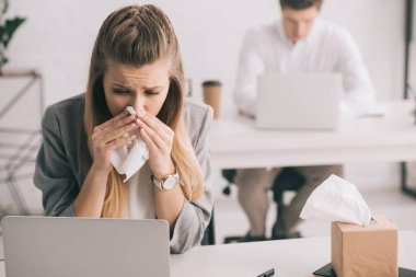 blonde businesswoman sneezing in tissue near coworker in office