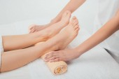 partial view of masseur doing foot massage to adult woman in spa