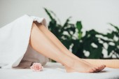 Fotografia vista ritagliata di donna adulta sdraiato sul lettino da massaggio in Spa