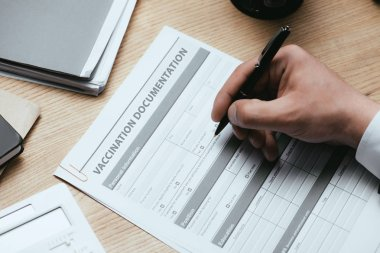 cropped view of man filling in Vaccination Documentation Medical Concept