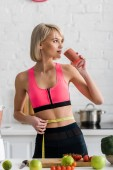blonde sportswoman drinking smoothie and holding measuring tape in kitchen