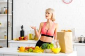 beautiful blonde woman standing in kitchen near fruits and vegetables