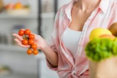 cropped view of woman holding cherry tomatoes in kitchen