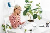 Fotografia pensieroso giovane bionda freelancer in occhiali tenendo penna e notebook mentre seduto vicino al computer portatile