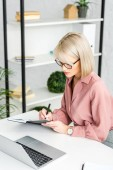 Fotografia pensiva giovane donna bionda in occhiali scrittura notebook mentre seduto vicino al computer portatile