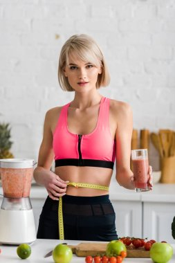 sportswoman holding glass with smoothie and measuring tape in kitchen