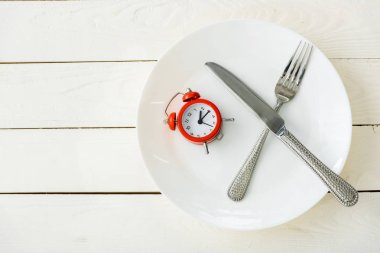 top view of white plate with cutlery and red alarm clock on wooden surface