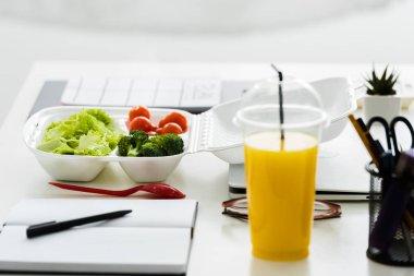 selective focus of organic vegetables near tasty orange juice
