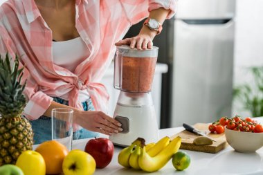 cropped view of woman preparing delicious smoothie in blender