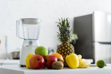 organic and tasty fruits near blender in kitchen