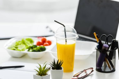 orange juice and green plants near tasty vegetables and laptop with blank screen