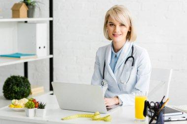 cheerful blonde nutritionist sitting near laptop and glass of fresh orange juice