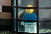 lego figurine with smiley face looking through window in block house