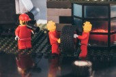KYIV, UKRAINE - MARCH 15, 2019: lego minifigures in red carrying tire while other figurine shouting in mouthpiece at service station