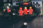 lego figurines of mechanics in red near tires at service station