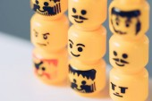 Selective Focus of yellow heads of lego figurines with various faces in rows