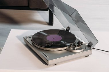 vintage vinyl record player on white table at home