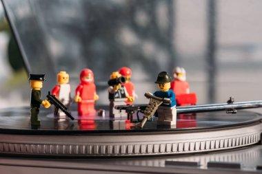 selective focus of plastic lego figurines fixing vinyl record player